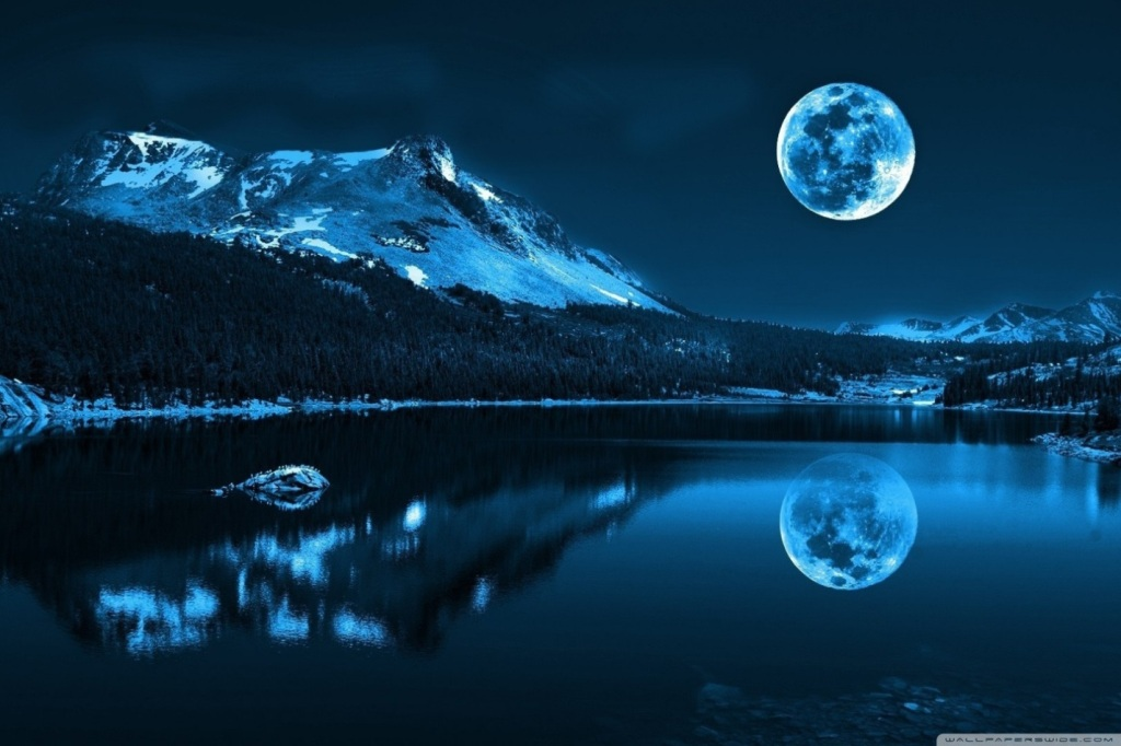 Full Snow Moon over still lake with Snowcovered peak in background